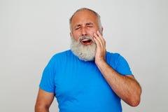 Skäggig man som trycker på hans kind som, om lida från tandvärk Arkivfoto