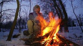 Skäggig man som värme hans händer vid branden i vinter Turist- manaftonlägereld arkivfilmer