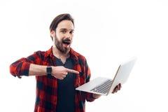 Skäggig maninnehavbärbar dator och peka på den royaltyfri bild