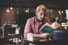 Skäggig manläsebok för Hipster i kafé royaltyfri foto