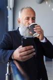 Skäggig manlig ålder av dricka kaffe 50-60 och att surfa i telefon Royaltyfria Bilder