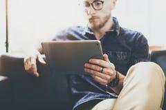 Skäggig marknadsföringsspecialist som arbetar för inredesign för digital minnestavla det moderna kontoret för vind Mannen kopplar royaltyfri bild