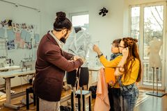 Skäggig modeformgivare som visar hans arbetsprocess till barn arkivbild