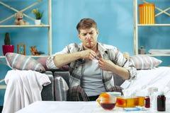 Skäggig sjuk man med rökkanalen som hemma sitter på soffan Sjukdomen influensa, smärtar begrepp home avkoppling Sjukvård royaltyfria foton