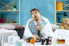 Skäggig sjuk man med rökkanalen som hemma sitter på soffan Sjukdomen influensa, smärtar begrepp home avkoppling Sjukvård royaltyfri fotografi