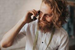 Skäggig skräddare som talar på telefonen Royaltyfria Bilder