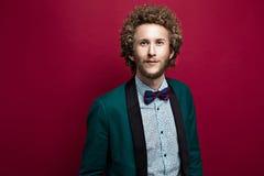 Skäggig stilfull man med den bärande flugan för lockigt hår, grönt omslag Röd bakgrund Arkivfoto