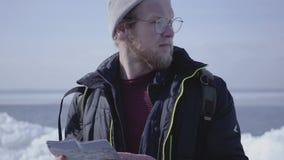 Skäggig stilig man för stående i varm omslag och hatt som går på glaciären som kontrollerar med översikten Förbluffa naturen av a arkivfilmer