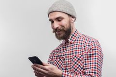 Skäggig stilig man som använder hans hörlurar, medan lyssna till musik royaltyfria bilder