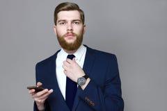 Skäggig stilig man som bär det smarta följet på en grå bakgrund Royaltyfri Fotografi