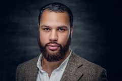 Skäggig svart man över grå bakgrund arkivbild