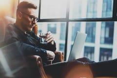 Skäggig ung affärsman som arbetar på det moderna kontoret Man som använder den moderna bärbara datorn horisontal suddighet bakgru Royaltyfria Foton