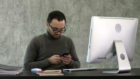 Skäggig ung affärsman som arbetar på det moderna kontoret Man som ser i hans smartphone och skriver något stock video