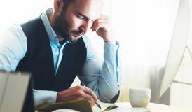 Skäggig ung affärsman som arbetar på modernt kontor Tänkande se för konsulentman i bildskärmdator Chefen skriver i noteboo Royaltyfri Foto