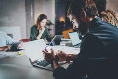 Skäggig ung coworker som arbetar på nattkontoret Man genom att använda den moderna bärbara datorn och skriva på den moderna smart Royaltyfri Fotografi
