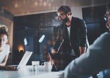 Skäggig ung coworker som arbetar på nattkontoret med partners Folk som använder den moderna bärbara datorn och den moderna smartp Arkivfoton