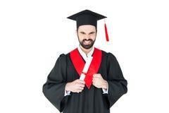 Skäggig ung man i hållande diplom för avläggande av examenhatt och se kameran Royaltyfri Foto