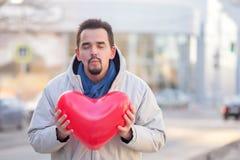Skäggig ung man med stängda ögon och klart att kyssa att rymma en röd ballon för hjärtaformluft i stadssteeten Urban romans arkivfoton