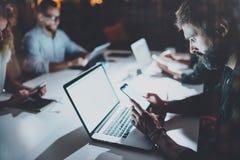 Skäggig ung man som arbetar på nattkontoret med partners Folk som använder den moderna bärbara datorn och moderna smartphones Royaltyfria Foton