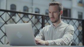 Skäggig ung man som framme sitter på tabellen på terrassen av bärbara datorn och att arbeta Begrepp av frilans- avlägset arbete arkivfilmer
