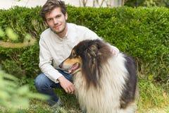 Skäggig ung man som utomhus knäfaller med den håriga colliehunden Royaltyfri Fotografi