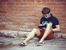 Skäggig ung stilfull hipsterman som använder minnestavlan arkivfoto