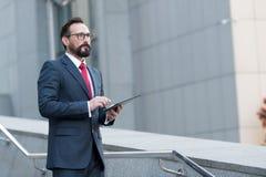 Skäggig yrkesmässig manmäklare som står utomhus-, medan rymma den digitala minnestavlan i hans händer Tänkande överblick för mode royaltyfri fotografi