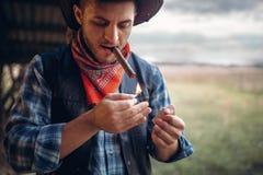 Skäggiga cowboyljus en cigarr, lös västra kultur arkivfoto