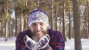 Skäggiga manslag snöar från gömma i handflatan och leenden stock video