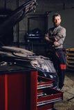 Skäggiga mekaniker med korsade armar som poserar nära en bil arkivbild