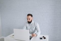 Skäggigt affärsmansammanträde på ett skrivbord i kontoret Fotografering för Bildbyråer