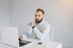 Skäggigt affärsmansammanträde på ett skrivbord i kontoret Arkivfoto