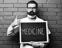 Skäggigt brutalt caucasian doktorsinnehavbräde med medicininskriften royaltyfria foton