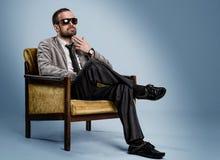 Skäggigt mansammanträde på en stol Fotografering för Bildbyråer