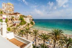 Skälla med en strand och hotell i Mallorca Royaltyfri Foto
