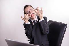 Skämtande för man för rolig affär som grimacing och grinar i kontoret arkivfoto