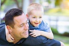 Skämtsam Caucasian fader och son som har gyckel på parkera Arkivbilder