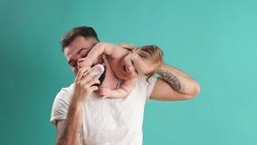 Skämtsam fader som bär hans le begynnande barn på hals över blå bakgrund lager videofilmer