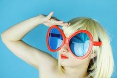 Skämtsam flicka med roliga exponeringsglas, lycklig stygg kvinna för blont hår Arkivfoto