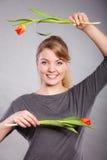 Skämtsam flicka som har gyckel med blommatulpan Arkivbild