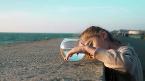 Skämtsam gullig liten flicka som ser fisken i fishbowl som spelar med henne i beachfront Begrepp av livstid stock video