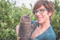 Skämtsam inhemsk katt som rymms och kelas, genom att le kvinnan med glasögon Utomhus- trädgård för inbrottgräsplanhem Grunt djup  royaltyfri fotografi