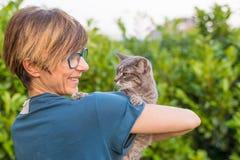Skämtsam inhemsk katt som rymms och kelas, genom att le kvinnan med glasögon Utomhus- trädgård för inbrottgräsplanhem Grunt djup  arkivbilder