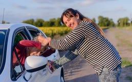 Skämtsam kvinna som drar håret av en kvinnlig chaufför Royaltyfri Bild