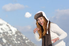 Skämtsam kvinna som kastar en snöboll i vinter på ferier Royaltyfri Bild