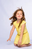 Skämtsam liten flicka i gult skratta för klänning Royaltyfri Foto