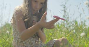 Skämtsam liten flicka som rotera ett spinnaresammanträde på grönt gräs på fält stock video