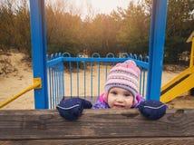 skämtsam lycklig liten flicka på lekplatsen royaltyfri bild