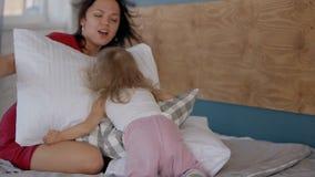 Skämtsam moder som sitter i kuddar på säng och den lilla dottern som finner henne stock video