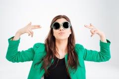 Skämtsam nätt ung kvinna i rund solglasögon som pekar på henne royaltyfri fotografi